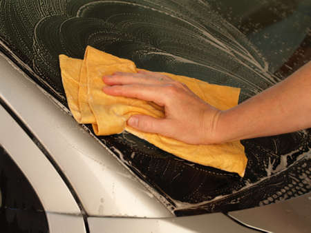 Man hand cleaning car with orange rubber photo