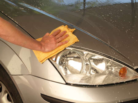 car cleaning: Cleaning the car with foam, water and rubber Stock Photo
