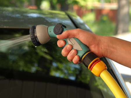 Car cleaning: man hand pouring a water  photo