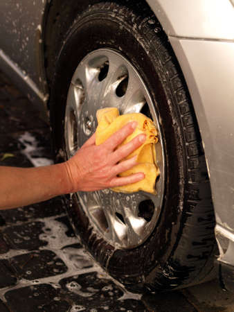 wash cloth: Washing the car wheel with foam and watter Stock Photo