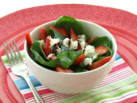 fruity salad: Bowl of salad with spinach leaves, strawberry pieces and feta