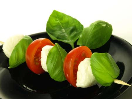 caprese salad: Caprese shashlik served on the black plate Stock Photo
