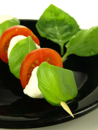 Close up of shashlik with mozzarella, tomatoes and basil photo