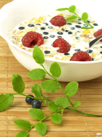 Milk with raspberries, blueberries and oat flakes photo