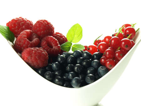 Bowl with summer fruits on isolated white background photo