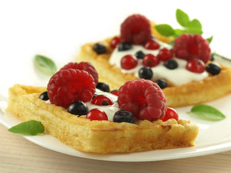 Two waffles with cream and fruits, closeup photo