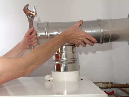 Ventilation: Ventilating pipe from condensing boiler in boiler room Stock Photo