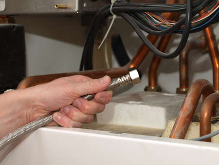 condensing: Man hand with cable inside the condensing boiler