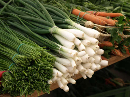 Bunches of vegetables on grocery tables outside photo