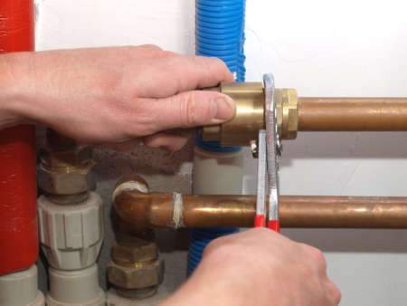 Worker hands fixing heating system with a special tool Stock fotó