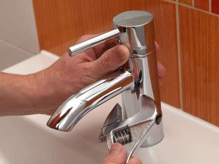 llave de agua: Plomero manos reparación agua del grifo con la llave