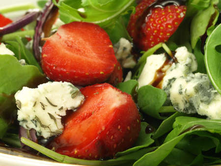 Strawberry pieces in cheese and spinach salad photo