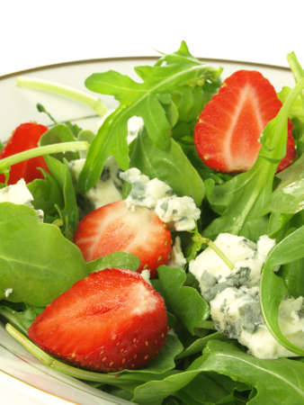 Gorgonzola cheese in spinach and strawberry salad, closeup photo