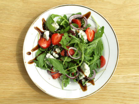Bird eye view of spinach salad with strawberries and onion photo