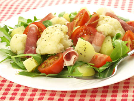 potato salad: Plate of cooked vegetables and parma ham rolls Stock Photo