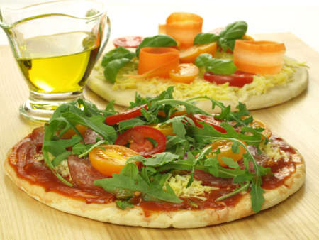 Prepared pizzas with vegetables and tomato sauce