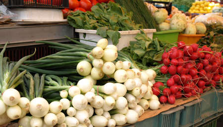 Outdoor market with stalls: onions and radish photo