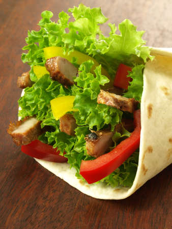 Closeup of tortilla wrap with meat and vegetables photo