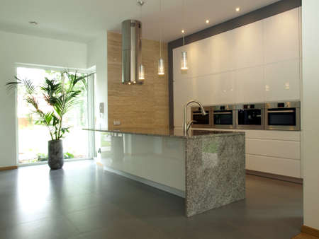 Bright well designed kitchen with travertine wall photo