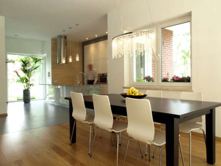 Modern kitchen and a dining room in a contemporary house. Stock Photo