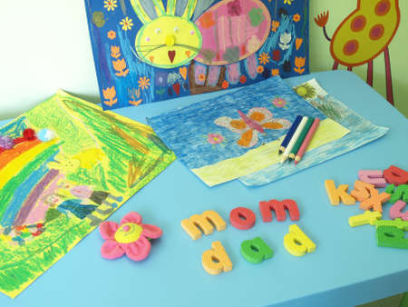 Table with paintings, crayons and colorful letters Stock Photo - 14608642