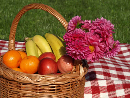 Basket of fruits and pink flowers on a fresh air photo