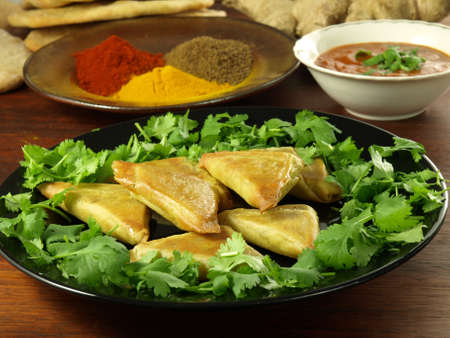 Indian appetizer: vegetable samosas with dip and hot spices photo