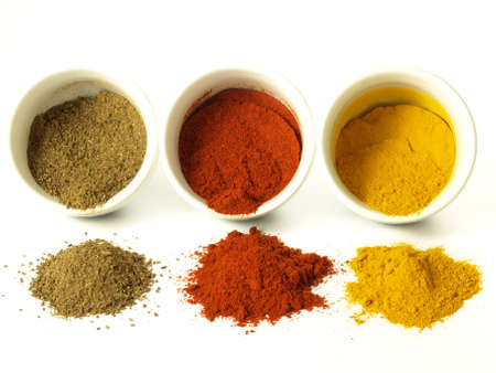 spices: Turmeric, cumin and hot pepper on isolated background