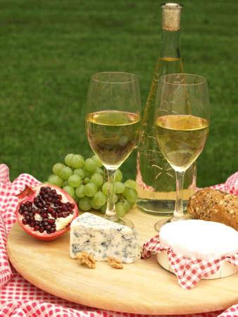 tabla de quesos: Tabla de quesos con queso, frutas y una botella de vino blanco Foto de archivo