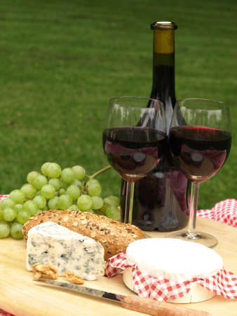 Glasses of red wine, cheese and grapes photo