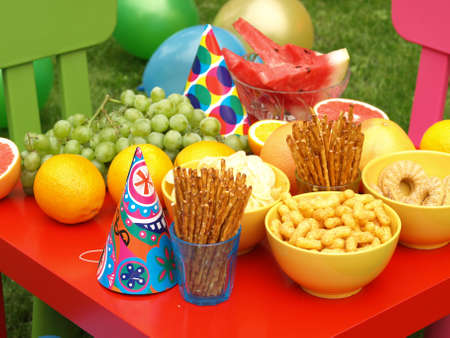 party table: Colorful equipment for a childrens party in garden Stock Photo