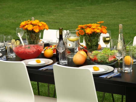 home party: Colorful laid table in a beautiful garden  Stock Photo