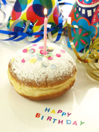 Donut with candle for birthday and confetti photo