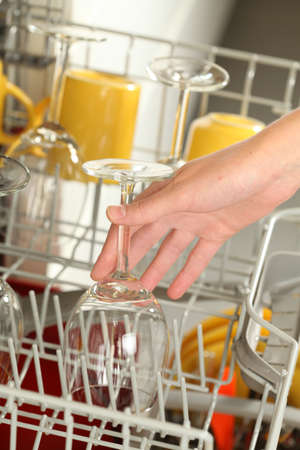 Woman's hand emptying or filling a dishwasher photo