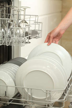 Womans hand taking clean plate from dishwasher Stock Photo