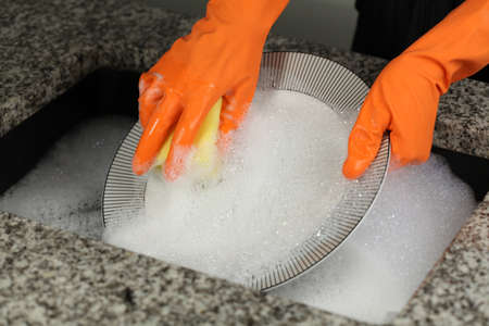dish washing: Womans hands in gloves cleaning a plate Stock Photo