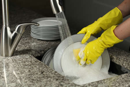 washing dishes: Closeup of washing a plates with protective gloves Stock Photo