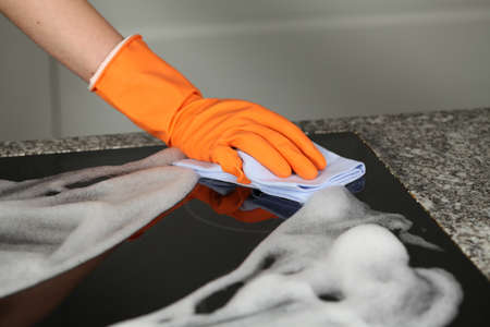 house cleaning: Hand in protective glove cleaning a stove