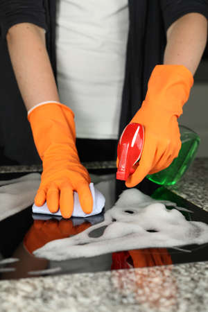 Womans hands cleaning a kitchen stove, closeup photo