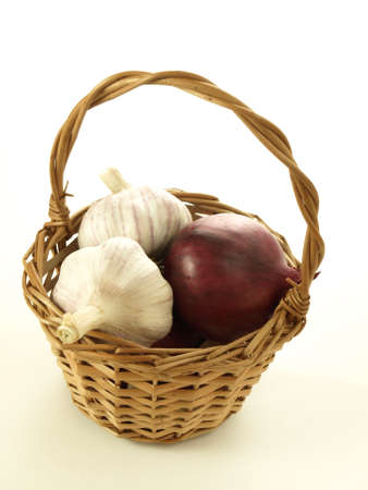 close up of onions in a basket: Onion and garlic in the wicker on isolated background