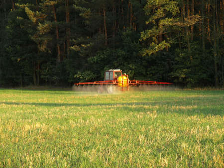 agronomics: Worker on a field spraying chemicals  Stock Photo