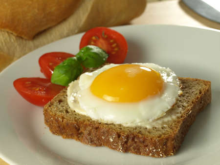 sunny side up: Sunny side up egg on a slice of bread with tomatoes on a plate with a French loaf in the background Stock Photo