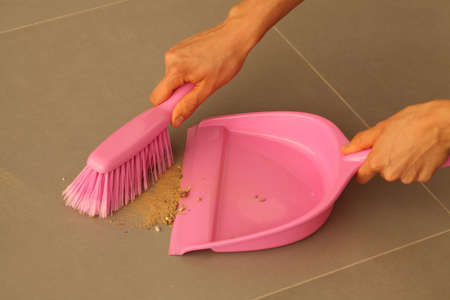 Housework with pink dustpan and brush, sweeping the floor photo