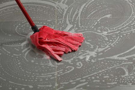 La limpieza de los azulejos del piso con un trapeador, las tareas domésticas en la cocina