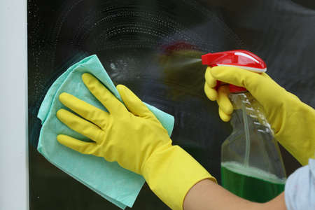 Female household,glass cleaning with rag and spray photo