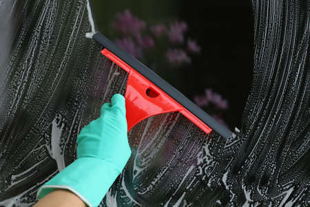 Housework with red squeegee for glass, window cleaning