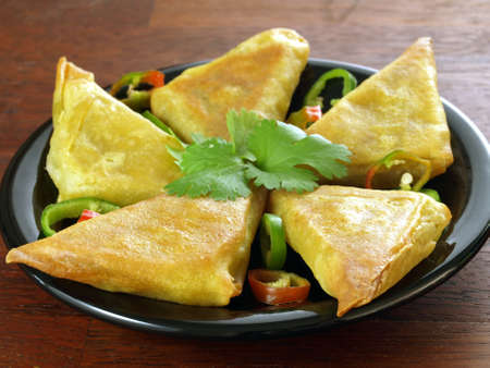 Indian appetizer: vegetarian samosas with coriander leaves
