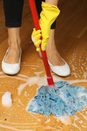 bright housekeeping: Perfect housewife in yellow gloves mopping wooden floor  Stock Photo