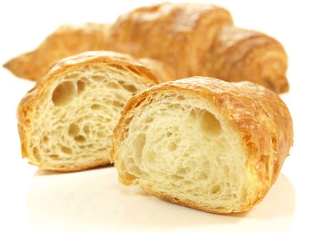 Croissant cut in half on isolated background photo