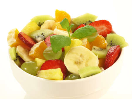 Pieces of fruits in bowl on isolated background photo